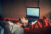 Young Adult Man in Despair Lying Down Next To Laptop With Falling Graph on It
