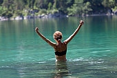 Happy Adult Woman With Arms Raised Walking Into a Lake