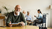 Senior man in eyeglasses smiling happily at camera while reading book sitting at table in assisted living home. Three elderly people including disabled woman playing cards in background