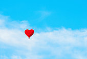 Red balloon in the the shape of heart in the blue sky. Background with concept of romance and St Valentines day