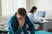 Frustrated middle aged male patient with heavy disease sitting on couch in doctors office while female physician in white coat making notes in his medical history in background