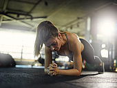Backlit shot of determined tired young woman doing forearm plank exercise during workout in gym