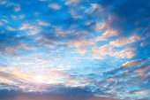 Sunset sky background. Picturesque pink colorful clouds lit by sunlight. Vast sky landscape panoramic scene