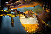 Male bartender pouring beer into glass