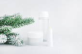 Skincare cosmetics bottles on snow covered surface. Winter season cosmetics. Blank containers with fir twigs backdrop. Christmas present for women idea. Banner. Copy space