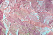 Silver purple green metallic foil multi-coloured creased and crumpled glossy holographic paper texture