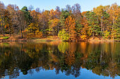 Autumn landscape with colorful trees reflected on the pond
