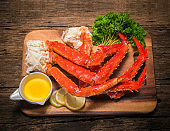 Cooked Organic Alaskan King Crab Legs with Butter and lemons, Alaskan King Crab on vintage wooden background.