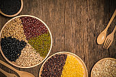 Various type of cereal grains,Wheat, rice, brown rice, buckwheat, barley, black sesame, millet,5 colors beans, black beans, red beans, white beans, green beans, soybean.on wood background