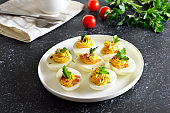 Deviled stuffed eggs with egg yolk, bacon, mustard and parsley