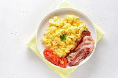 Scrambled eggs, fried bacon and tomatoes on plate