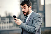 Businessman using smart phone and walking down the street