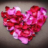 Heart shaped red rose petals. Greeting card for the holiday.