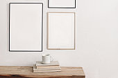 Set of black portrait picture frame mockups. Wall art gallery. Cup of coffee on pile of books on old wooden bench, table. White wall background. Scandinavian interior, neutral color palette.