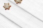 Christmas fabric mockup scene. Closeup of white folded muslin cotton textile. Star shaped gingerbread cookies with decorative sugar frosting. Holiday background. Flat lay, top view.