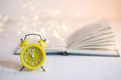 Yellow alarm clock and book on a white table.
