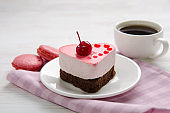 souffle cake in the shape of heart  with cup of coffe and macaroons on a wooden table