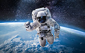 Astronaut in the outer space over the planet Earth. Elements of this image furnished by NASA