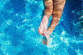 Girl's feet inside a blue swimming pool in summer, copy space.