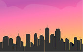 silhouette  of a rising city and dawn in the background