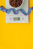 Raisins, centimeter tape, scales on a yellow background. The concept of a healthy diet. Flat lay, copy space