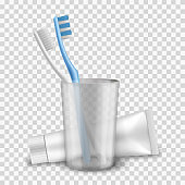 Toothbrushes white and blue are in cup near toothpaste tube mockup. Oral hygiene products.