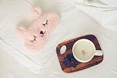 Cup of coffee with cute pink sleep mask