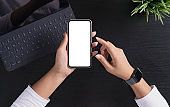 focus on hand holding phone showing white screen on top view