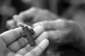 Cross in hand, deep connection with God concept in black and white.