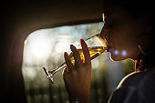 Businesswoman traveling by car and drinking champagne in the back seat