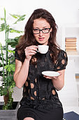 Passionate about coffee. Pretty woman drinking coffee in office. Sexy business woman with teacup sitting on desktop. Sexi woman employee enjoying hot beverage during working break. Woman in business