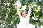 Happy girl in fashion dress pose at green tree. Little child smile with long blond hair outdoor. Kid model with fresh face skin in summer nature. Fashion beauty and hairstyle. Skincare and freshness