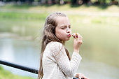 Enjoying every bite. Kid girl eat cookie. Health and dieting concept. Dieting counting calorie. Break her diet for sweets. Outdoors snack. Delicious cookie healthy snack. Sweet cookie pure enjoyment