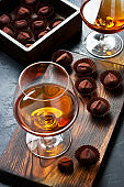 Whiskey or cognac  in  glass with  truffles candy on  dark background