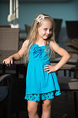 small smiling baby girl in blue dress near cafe table