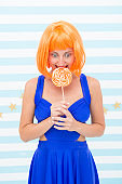 Crazy girl in playful mood. happy pinup model with lollipop in hand. Fashion girl with orange hair having fun. Cool girl with lollipop. Sexy woman. So much fun. Crazy party girl. Fun time