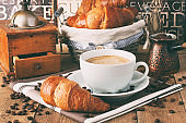 Composition with coffee cup and croissants