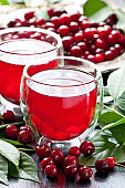 Fresh cherry juice in  glass, cherry berries with leaves