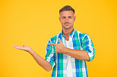 this is beat offer. presenting product. goods for men. summer sales here. man yellow wall. mature man unshaven face. smiling guy pointing finger, copy space. male fashion model checkered shirt