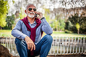 An elderly man is talking on a mobile phone outdoors