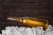 Bottle of cold light beer in ice cubes at the wooden background. Quenching thirst. Advertising.