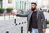 Businessman catching taxi while standing outdoors urban background. Man bearded hipster casual style waiting for taxi. Guy at street city center. Looking for transportation. Bus stop. Need a taxi