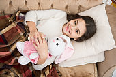 Girl enjoy evening time with favorite toy. Kid lay bed and hug bunny toy couch pillow blanket background top view. Girl child wear pajamas hug bunny. Play soft toy before go sleep. Sleep with toy