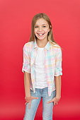 Shy beauty. Happy childhood. Girl cute child smiling face expression on red background. Positive emotions concept. Happy childrens day. Being happy every day. Schoolgirl casual style emotional kid