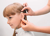 doctor adjusting of a hearing aid for little girl