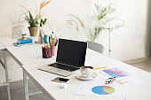 Photo of laptop and white cup of coffee on desk in modern empty office. Comfortable and cozy workplace