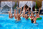 Multiracial group of friends having party in private villa swimming pool. Happy young people in swimwear dancing and splashing with inflatable floaties at luxury resort on sunny day. Girls in bikini