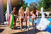 Hot pretty girls in bikini walking together with inflatable swan, swim ring by swimming pool. Attractive slim women in swimsuits have fun relaxing on sunny day summer party at luxury resort or villa