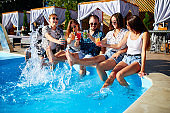 Group of friends having fun at poolside party clinking glasses with fresh cocktails splashing water by swimming pool on sunny summer day. People drinking beverages at luxury villa on tropical vacation