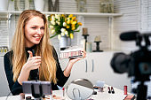 Beauty blogger woman filming daily make-up routine tutorial near camera. Influencer girl live streaming cosmetics product review. Vlogger female recommends eye shadow palette showing thump up sign